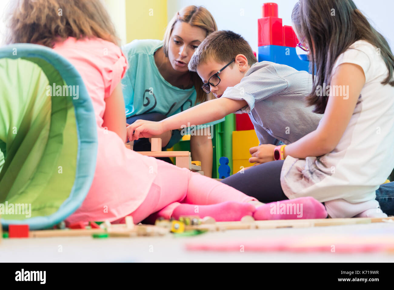 Pre-school boy coopérant avec les enfants sous la direction d'kindergar Banque D'Images