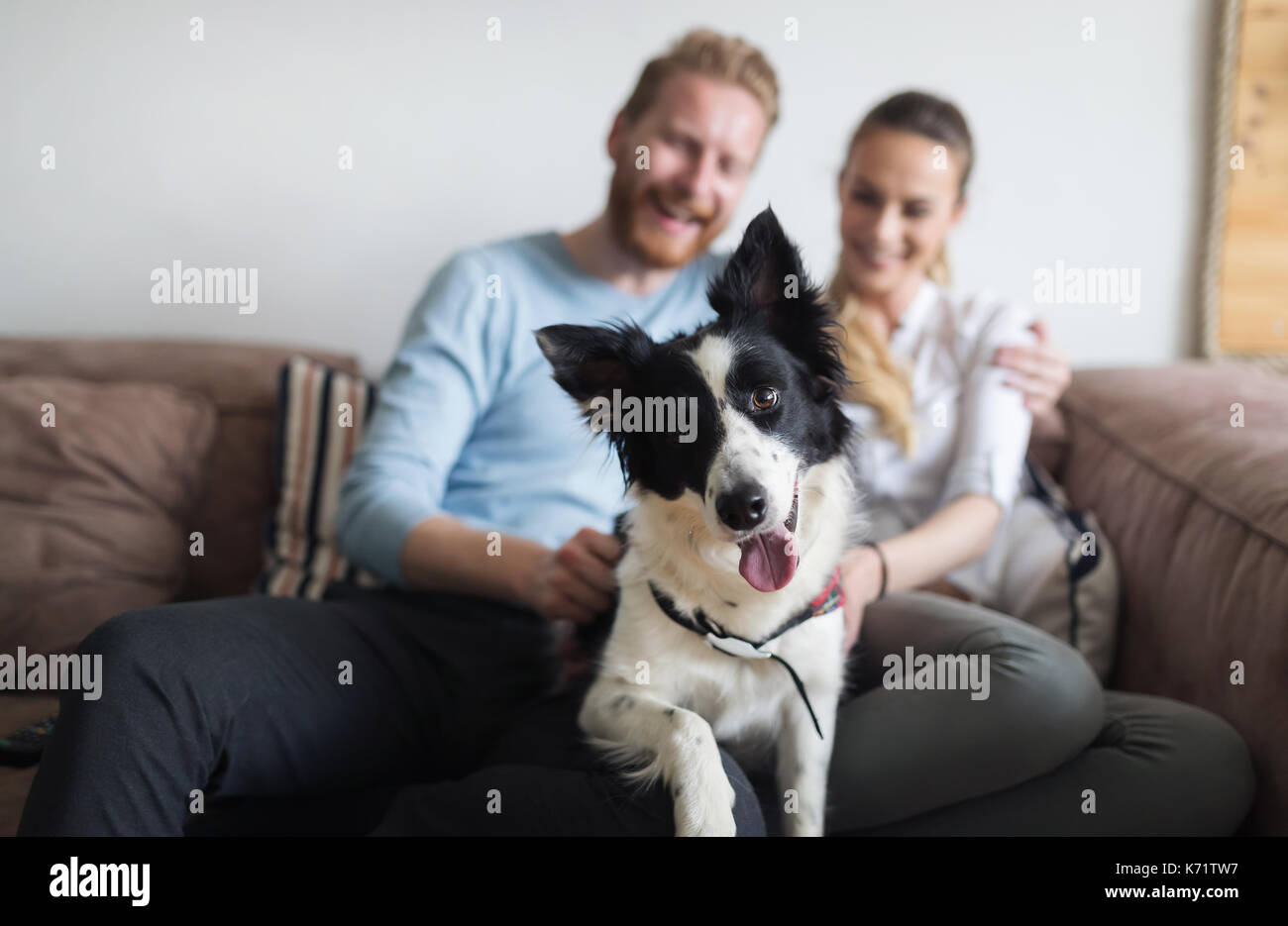 Beau couple relaxing at home et d'aimer leur chien Photo Stock