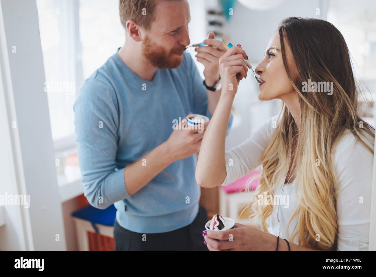 Couple et de rire à la maison tandis que la consommation de crème glacée Banque D'Images