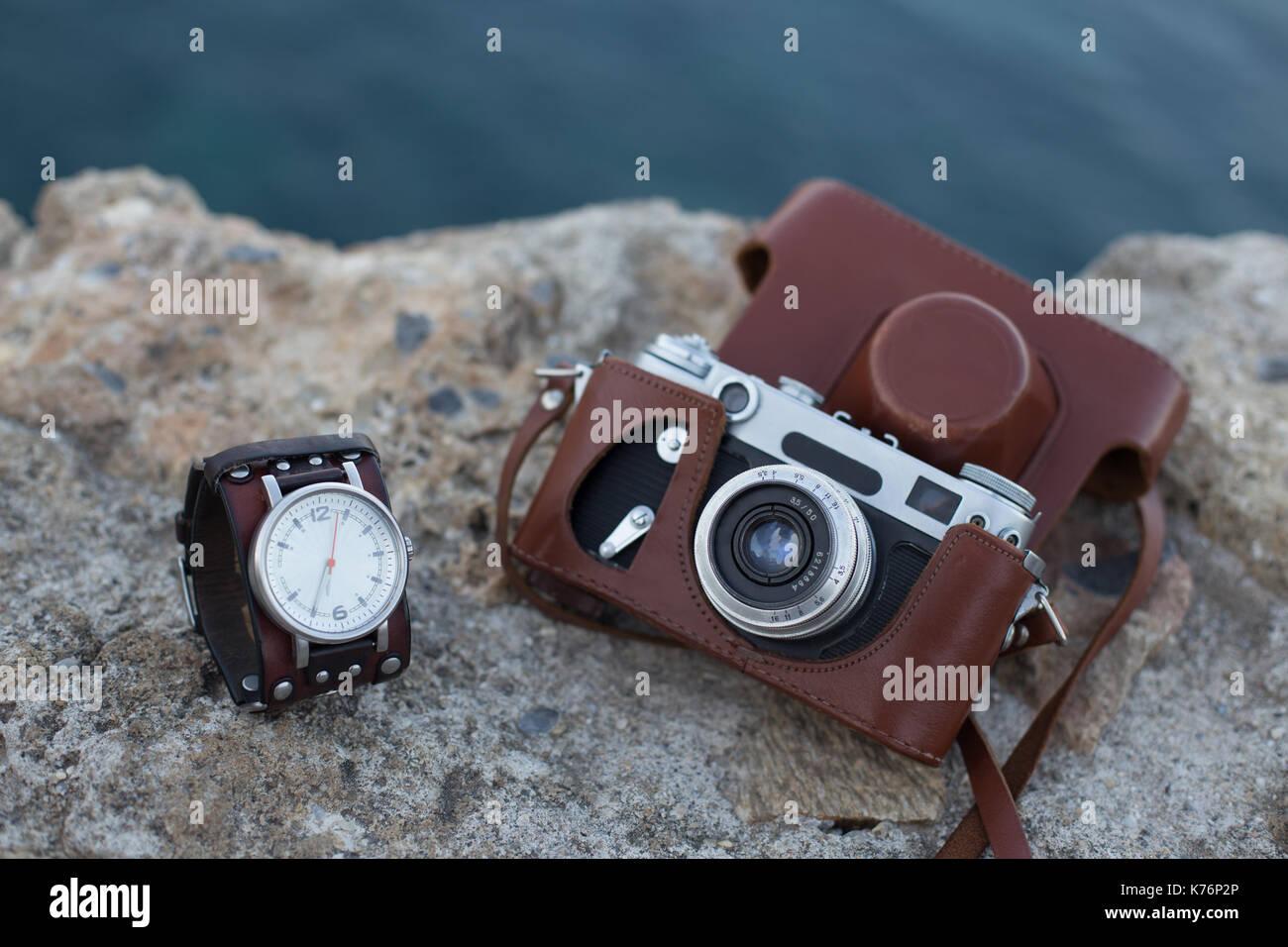Old vintage film appareil dans étui en cuir brun et Montre à bracelet en cuir placé sur la surface de pierre Photo Stock