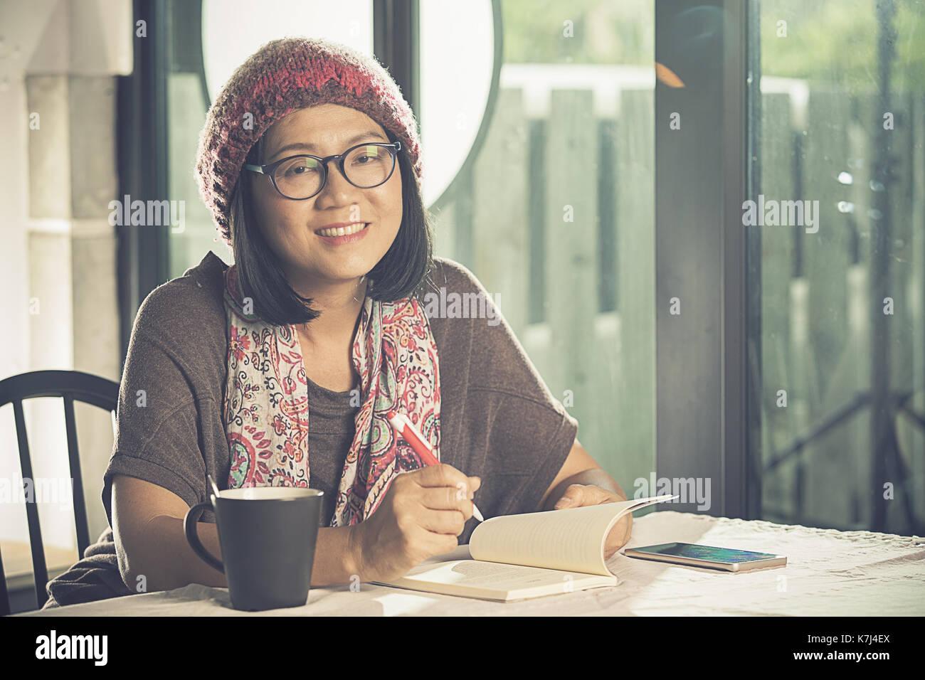 Dents sourire de femme asiatique livre de poche lecture in coffee shop Photo Stock