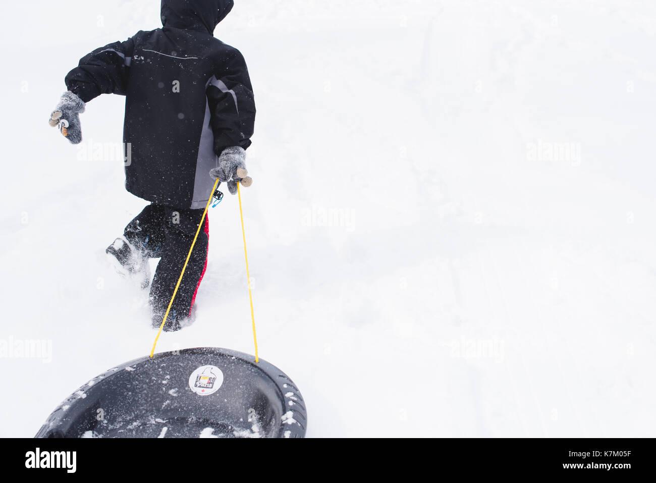 Jeune garçon tirant un traîneau d'une colline couverte de neige en hiver. Photo Stock