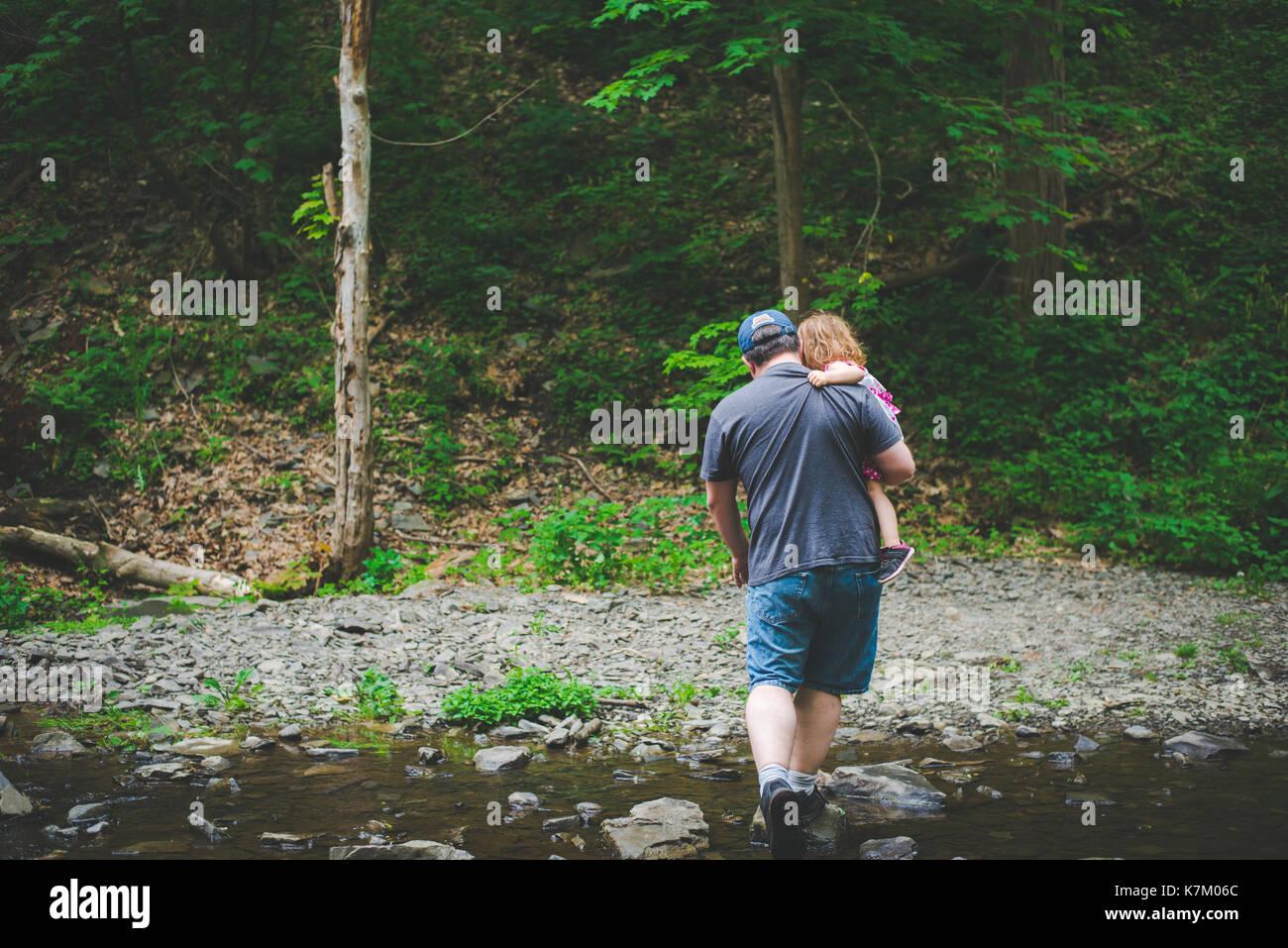 Un père porte sa fille lors d'une randonnée dans les bois. Photo Stock