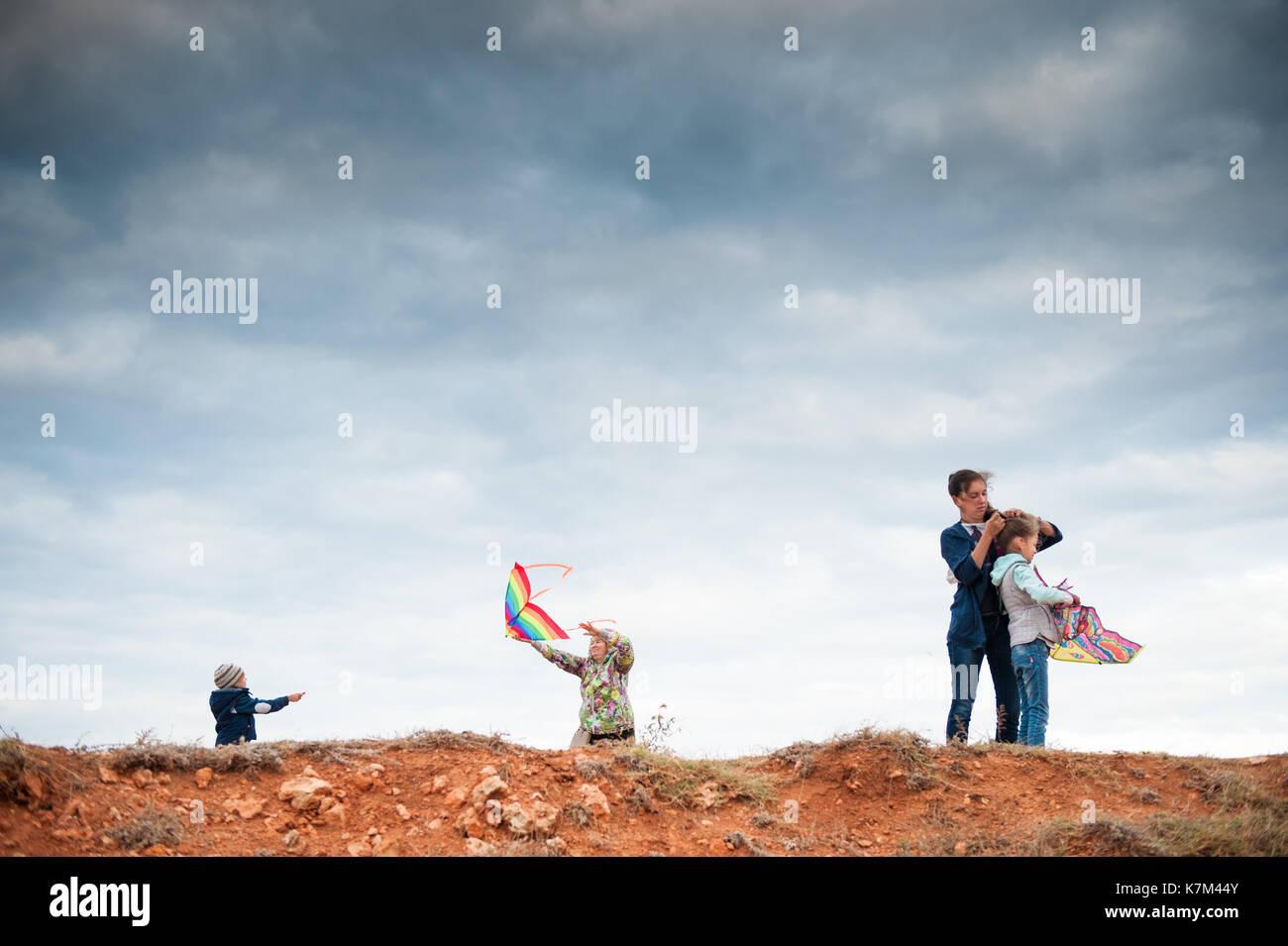 Famille heureuse de jouer avec trois générations d'extérieur Cerfs-volants Photo Stock
