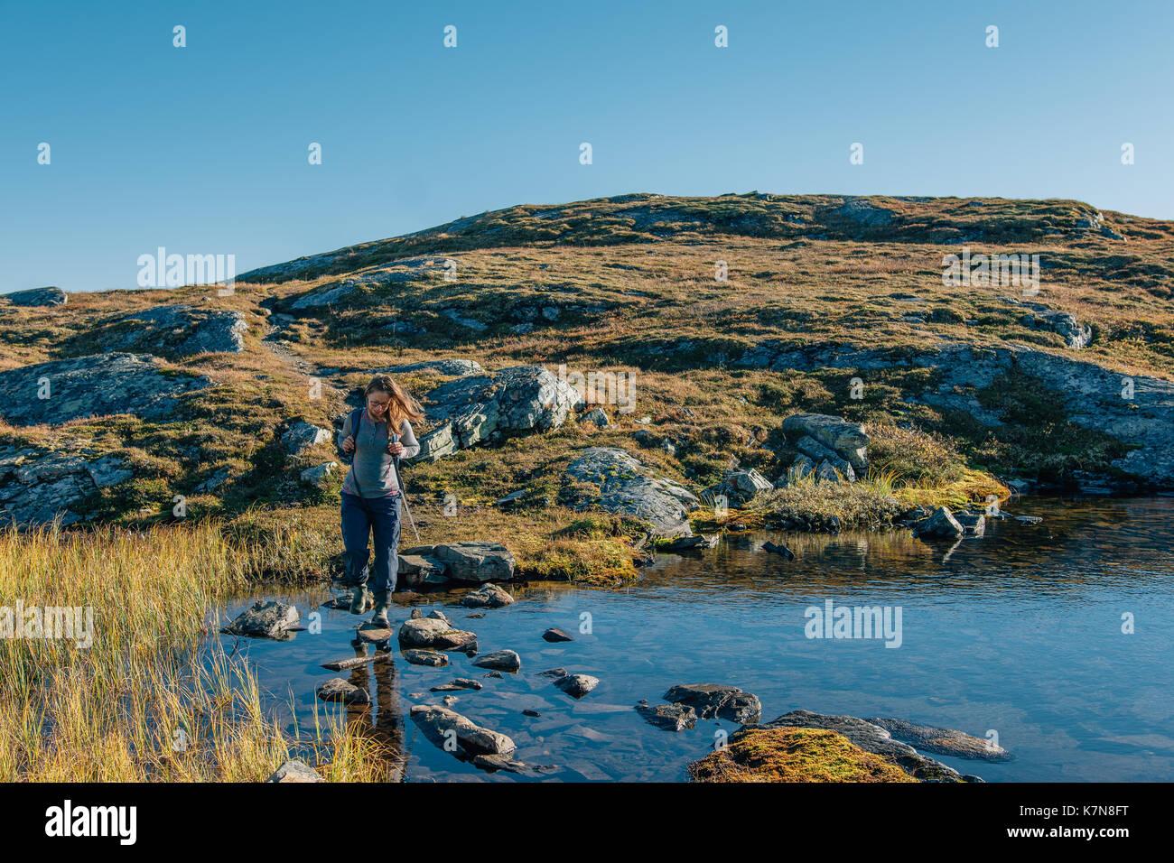 Jeune femme avec sac à dos de randonnée en pleine nature suédoise Photo Stock