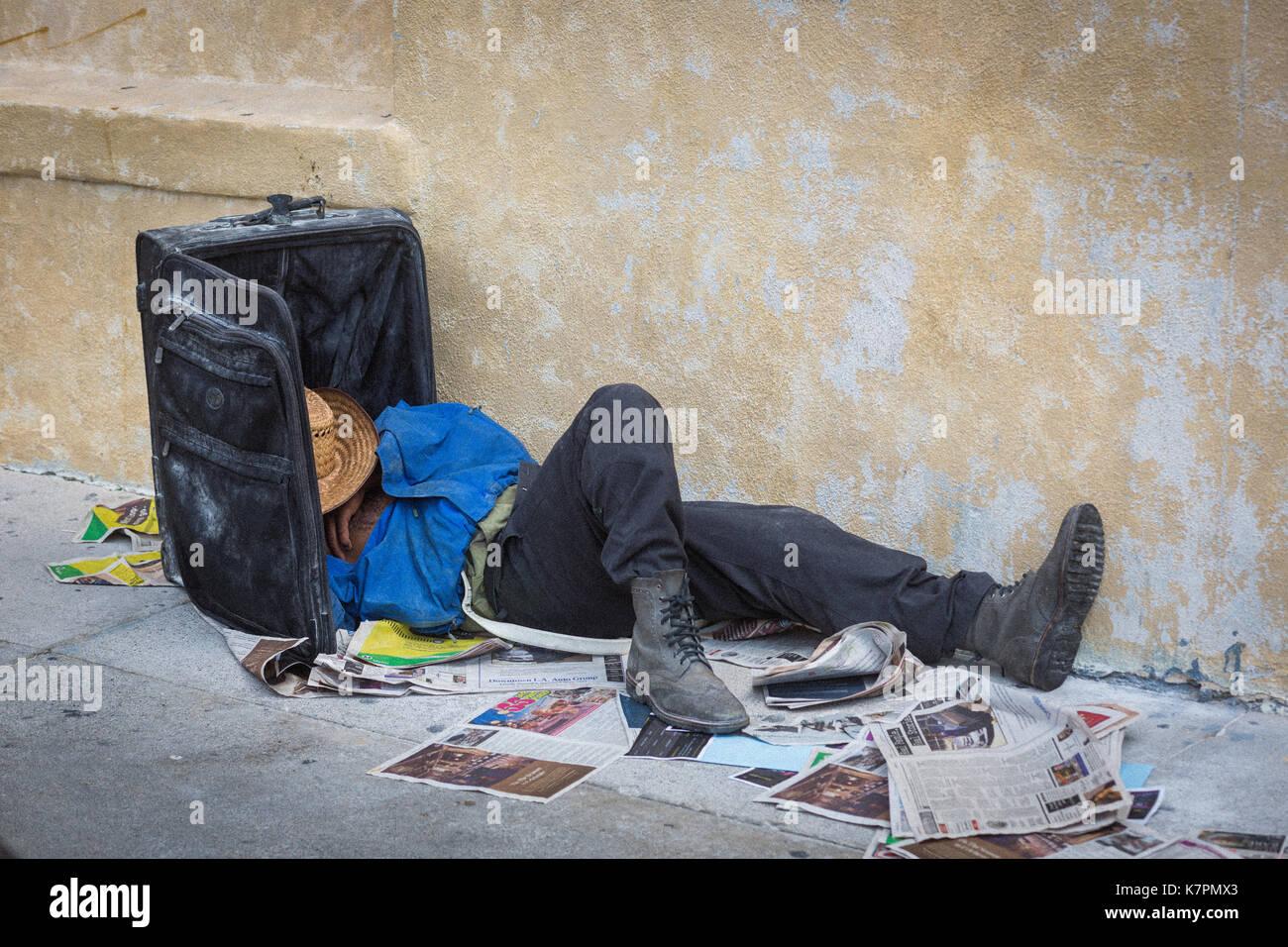 Homme couché avec la tête dans la valise, vraisemblablement, sans-abri au centre-ville, los angeles, dans le quartier de la mode, près de Skid Row. Photo Stock