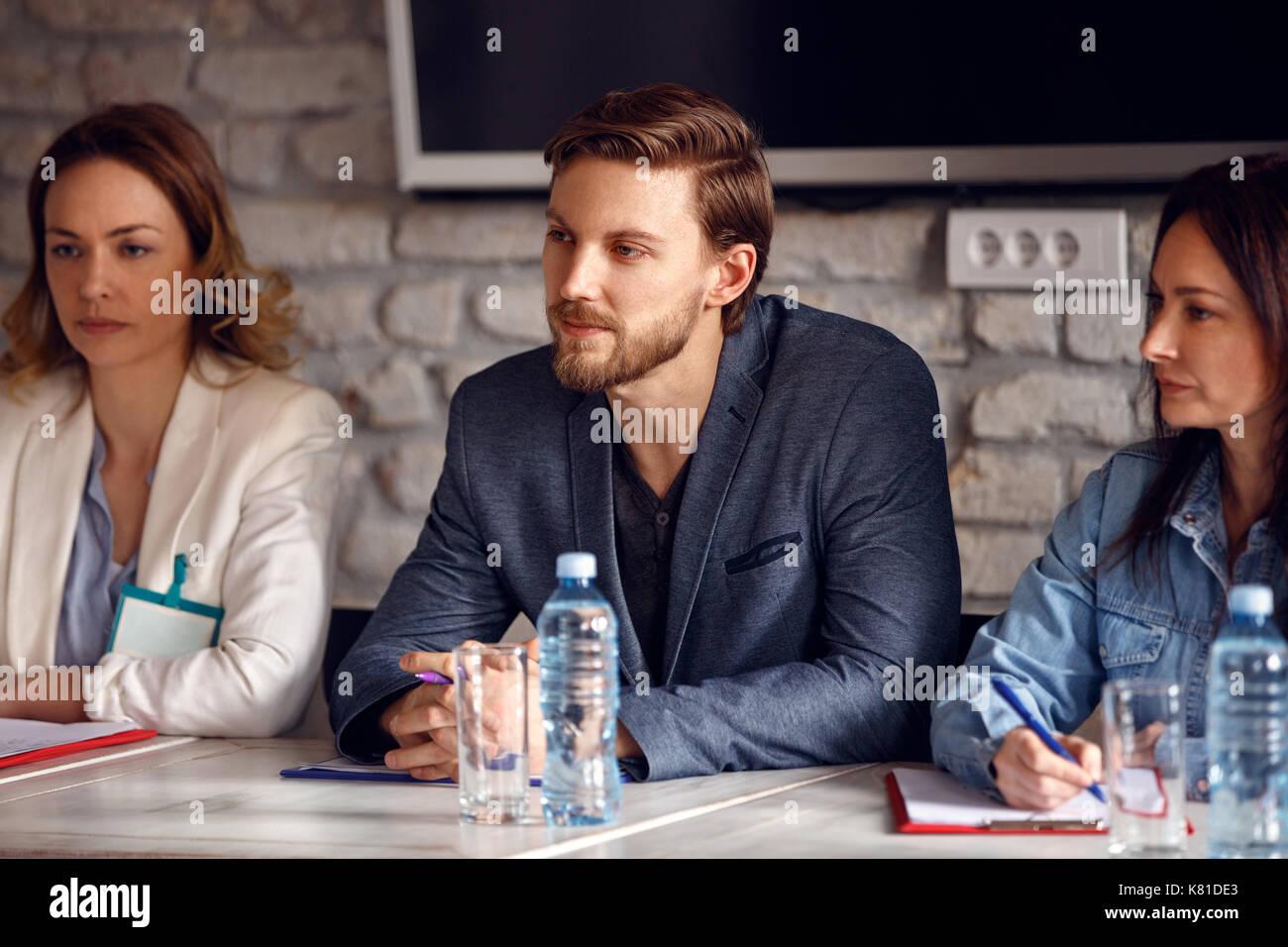 Homme sérieux avec deux collègues de sexe féminin dans la commission pour l'emploi en entreprise Photo Stock