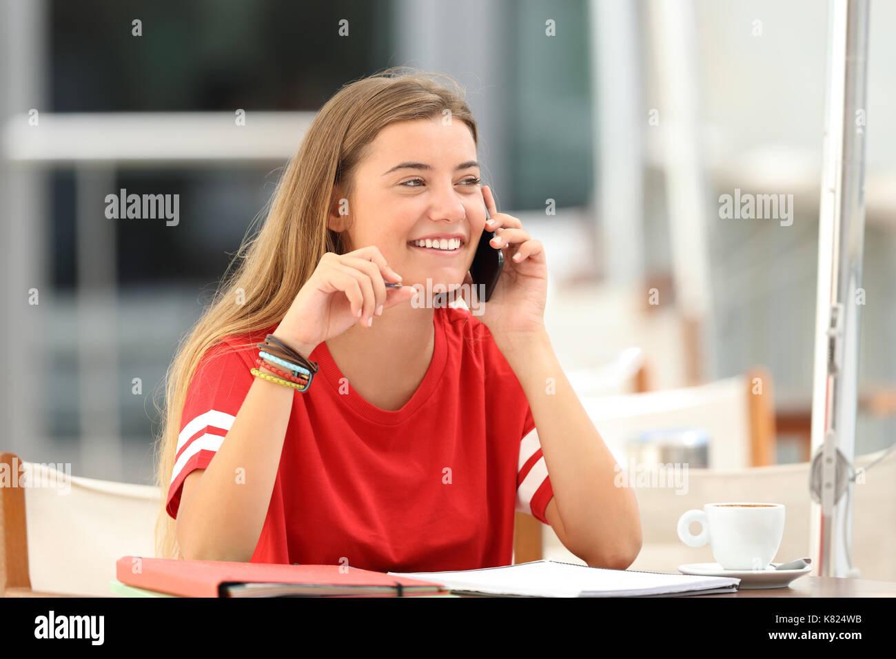 Étudiant candide girl laughing parlant au téléphone de l'emplacement dans un bar terrasse Photo Stock