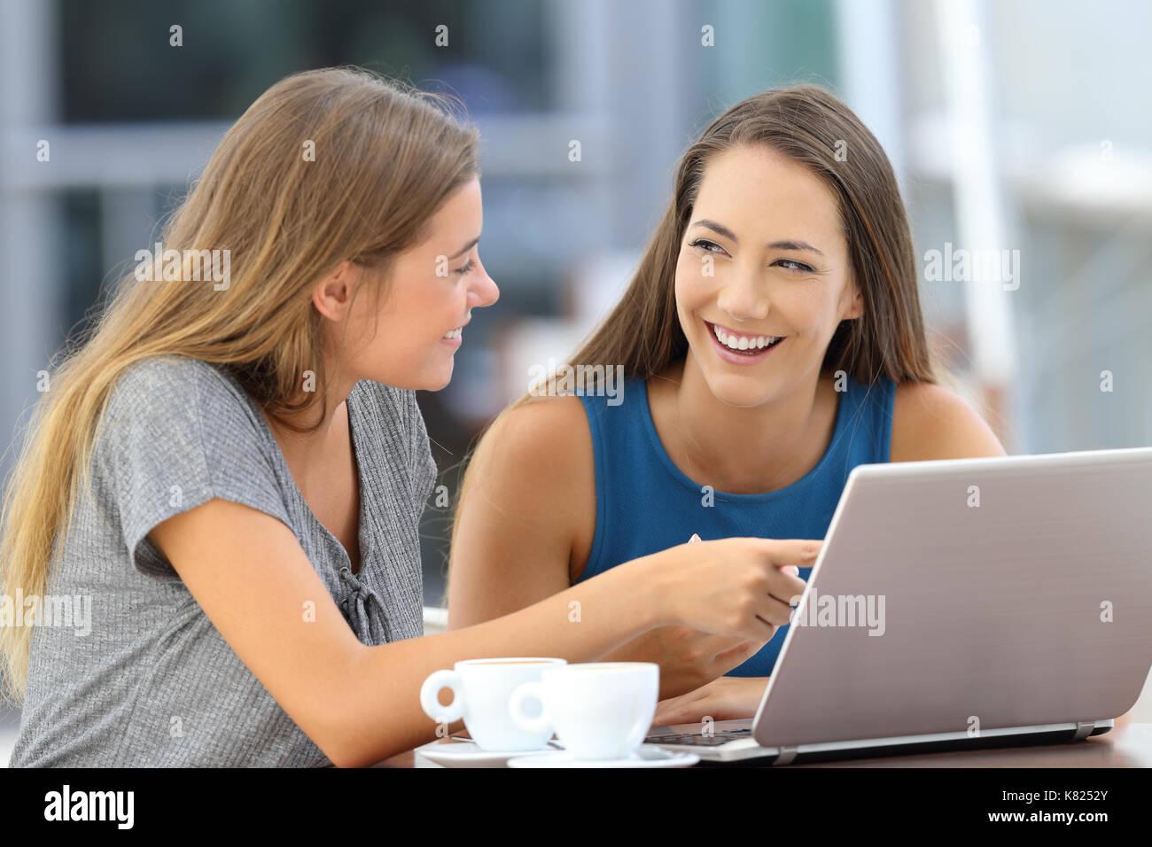 Deux amis heureux de parler de contenu en ligne assis dans un bar terrasse Photo Stock