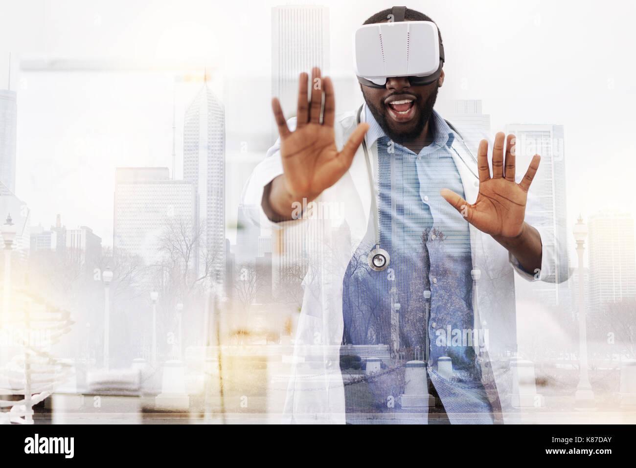 Cheerful doctor en utilisant la réalité virtuelle mask Banque D'Images