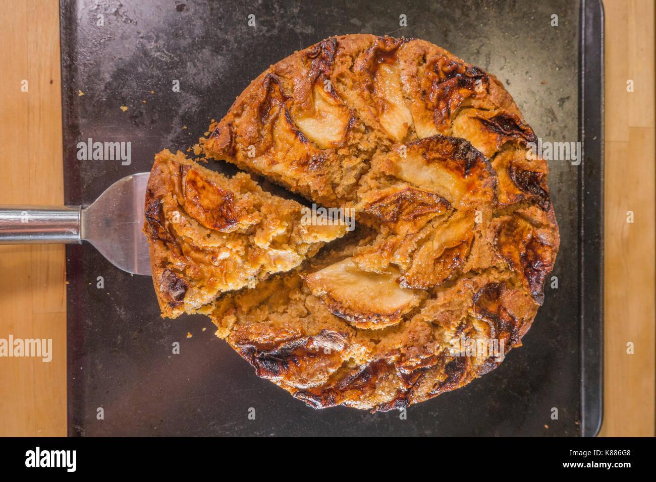 Une coupe triangulaire de gâteau aux pommes épicées, de refroidissement sur une plaque de cuisson dans une cuisine, de l'étuve. Angleterre, Royaume-Uni. Photo Stock