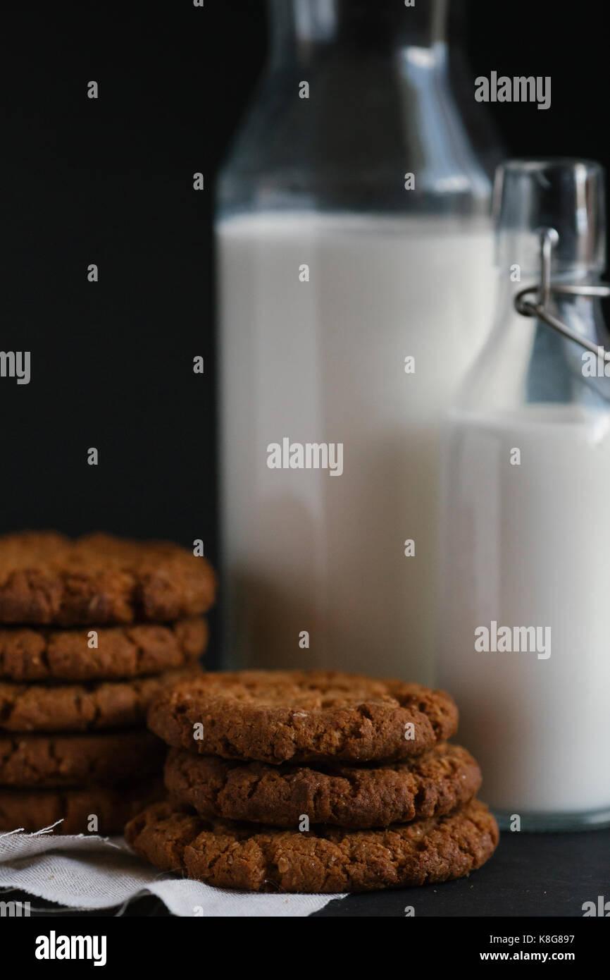 Close-up des cookies et du lait sur la table sur fond noir Photo Stock