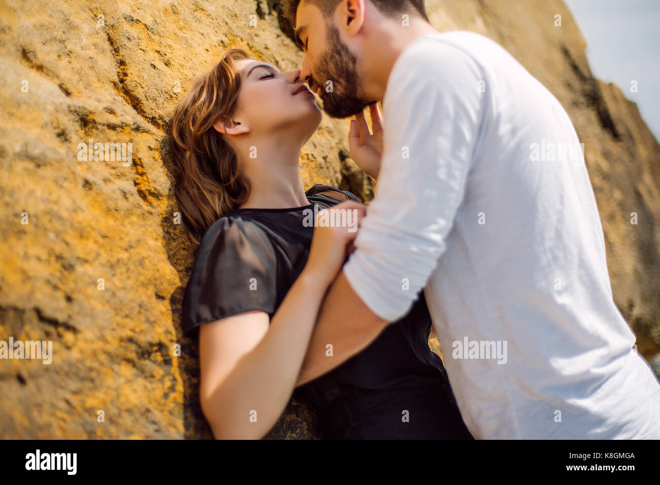 Couple kissing on rock Photo Stock