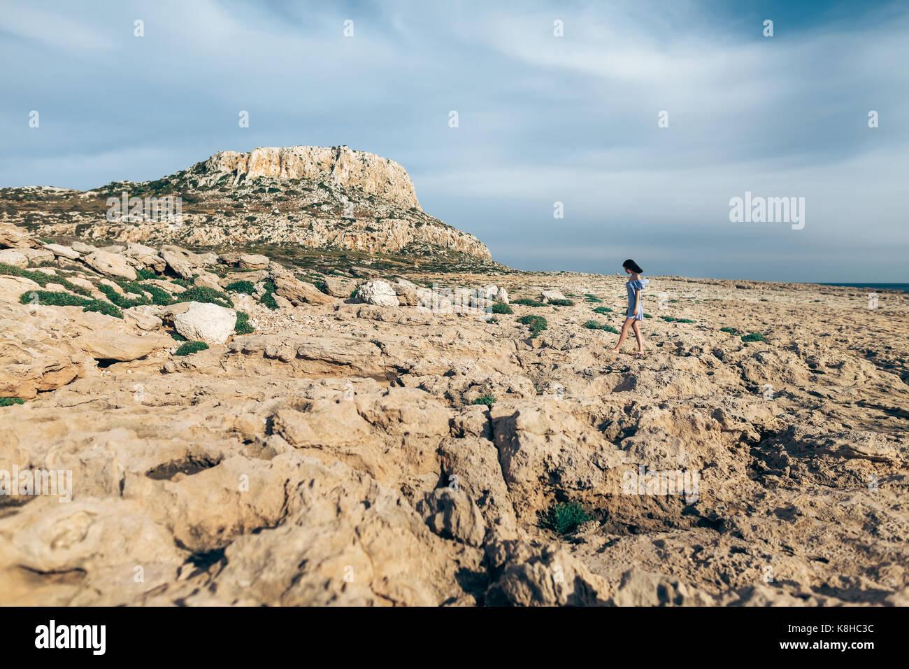 Belle femme marche sur le seul désert rocheux avec ciel dramatique Photo Stock