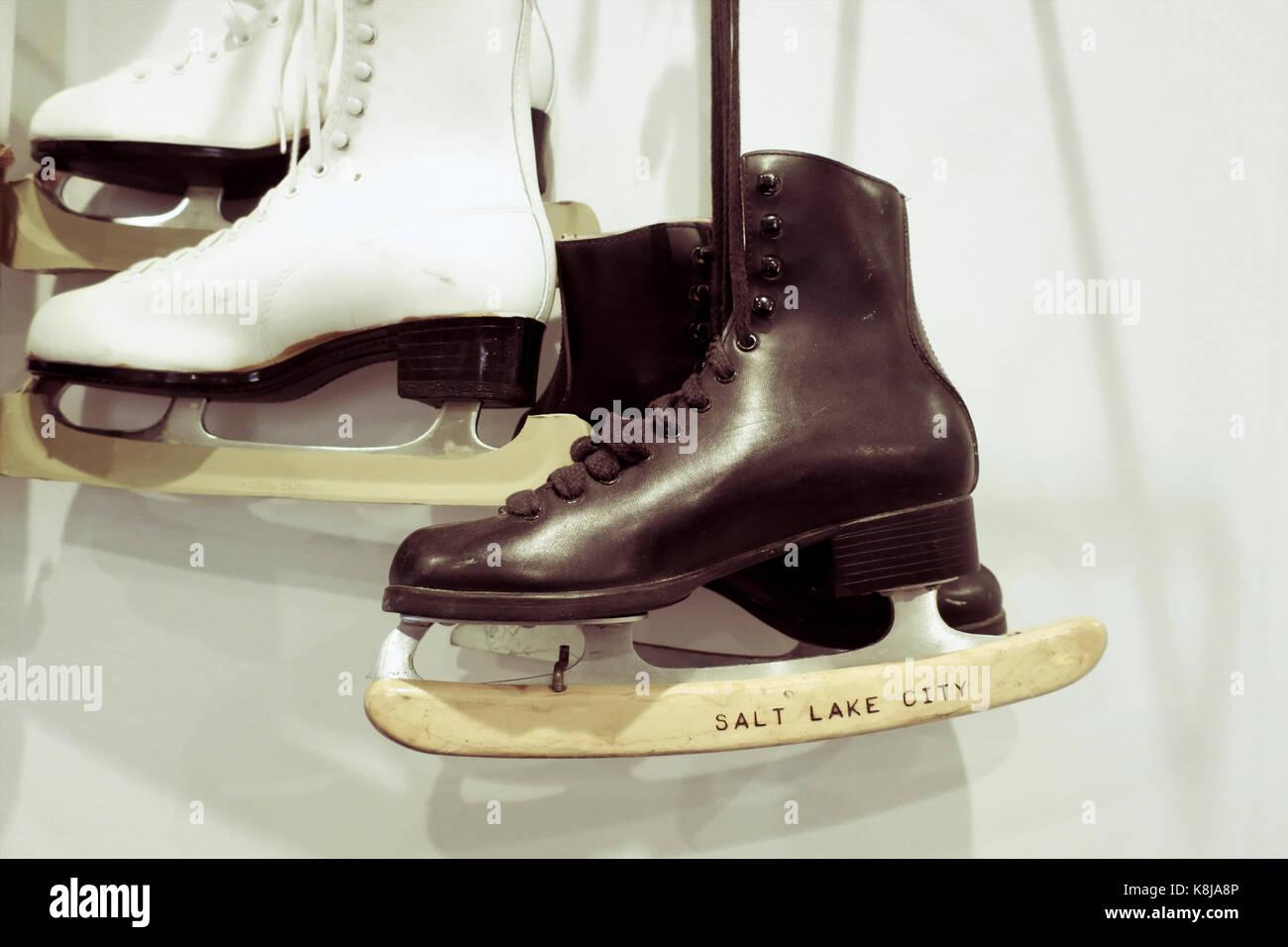 Deux paires de patins à glace à l'ancienne accroché au mur. Photo Stock