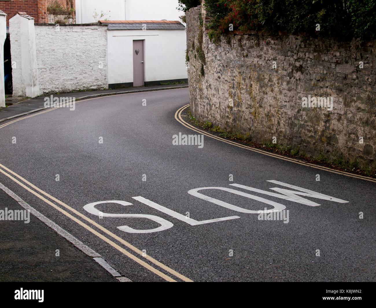 Le marquage routier lente peint sur un revêtement routier Photo Stock