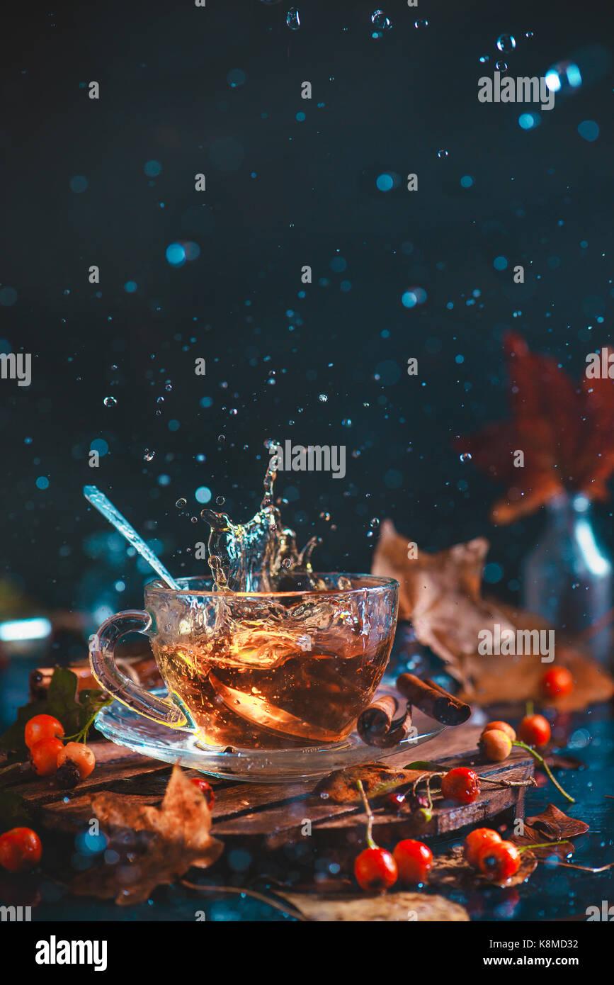 L'automne d'action place de la tasse de thé, de feuilles d'automne, coaster en bois et des baies, Photo Stock
