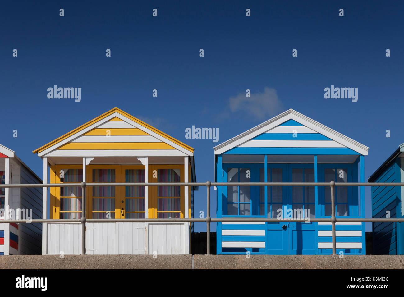 Deux cabines de plage une jaune, une bleue sur le front de mer de Southwold, Suffolk, Angleterre Banque D'Images