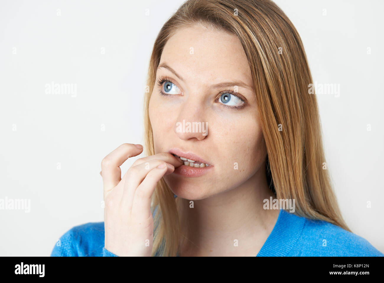 Studio shot of woman biting nails nerveux Photo Stock