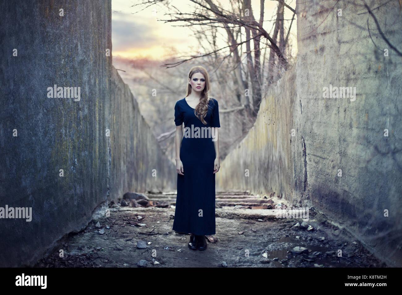 Belle jeune fille solitaire en robe longue près de tunnel sombre sur le coucher du soleil Photo Stock