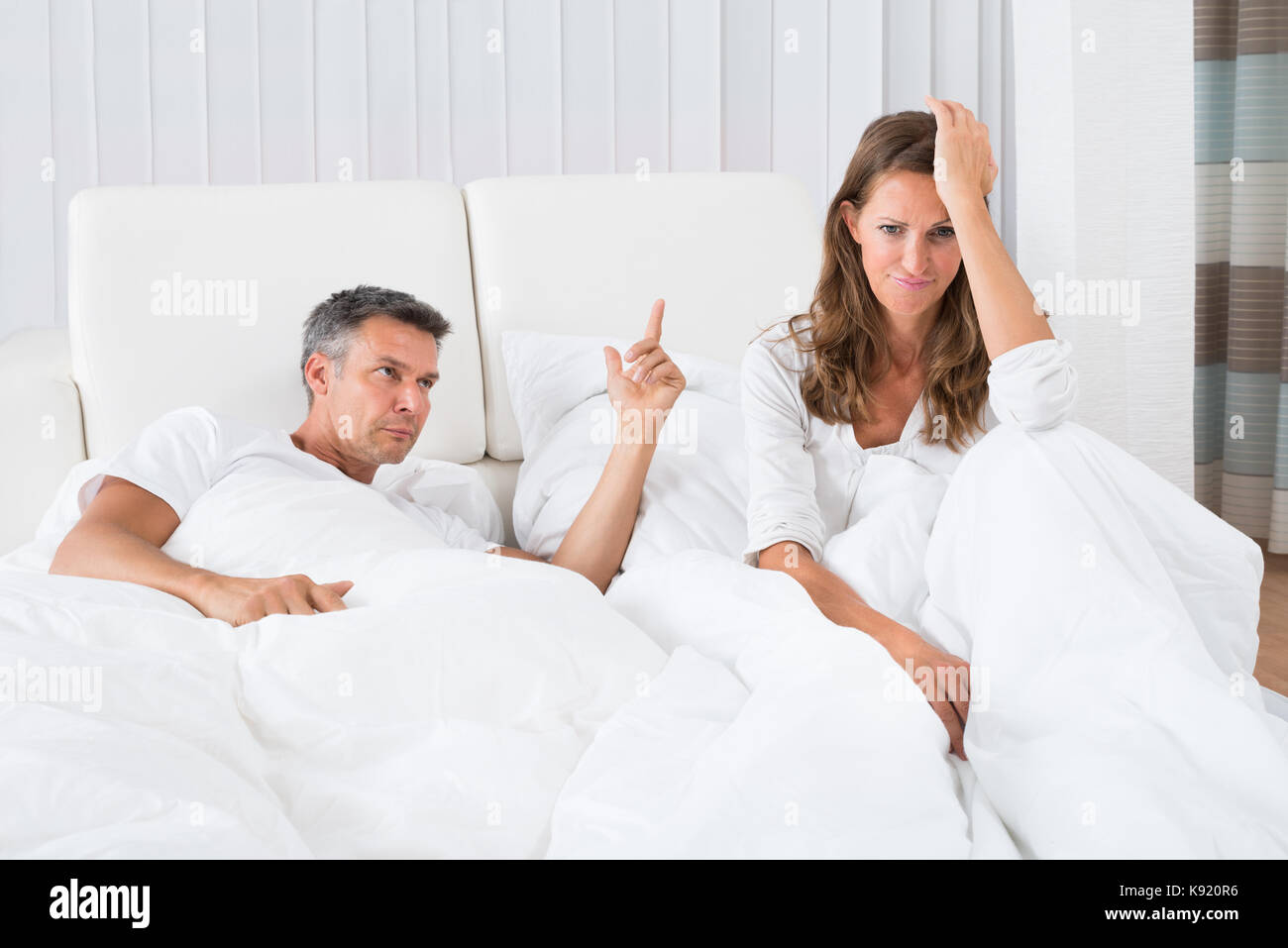 L'homme en faisant valoir avec woman sitting on bed Photo Stock