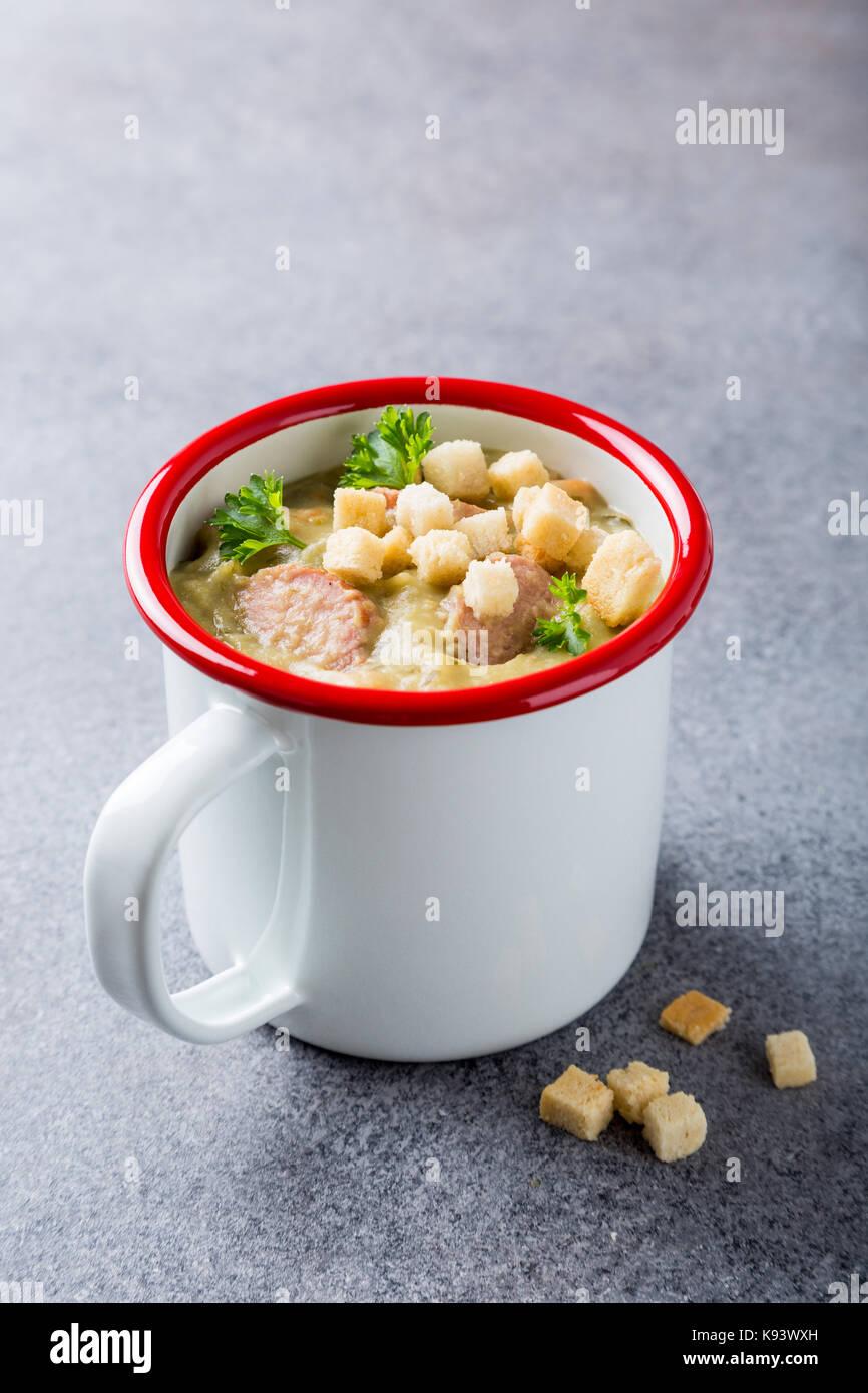 Soupe aux pois maison avec de la saucisse et croûtons Photo Stock