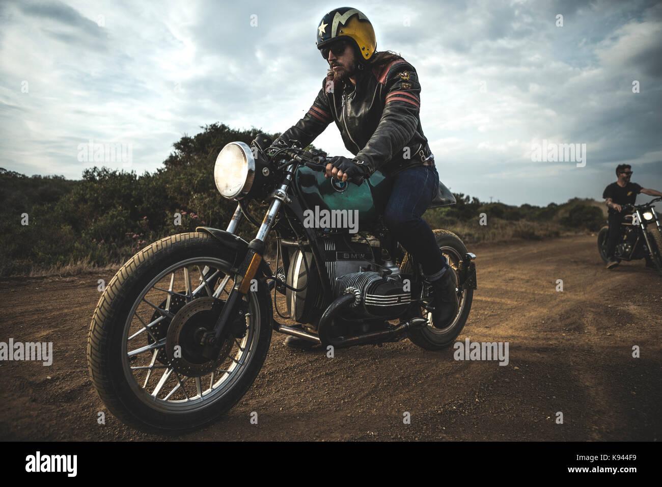 homme portant face ouverte casque et lunettes quitation cafe racer moto sur une route de terre. Black Bedroom Furniture Sets. Home Design Ideas