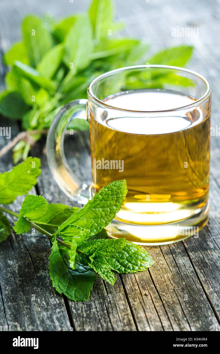 Thé à la menthe délicieux. Les feuilles de menthe et tasse de thé. Banque D'Images