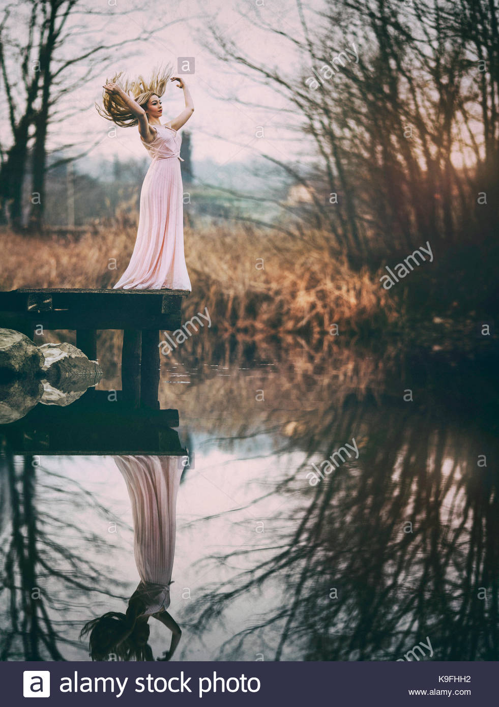 Dame en robe rose par un étang: beauté dans la nature Photo Stock
