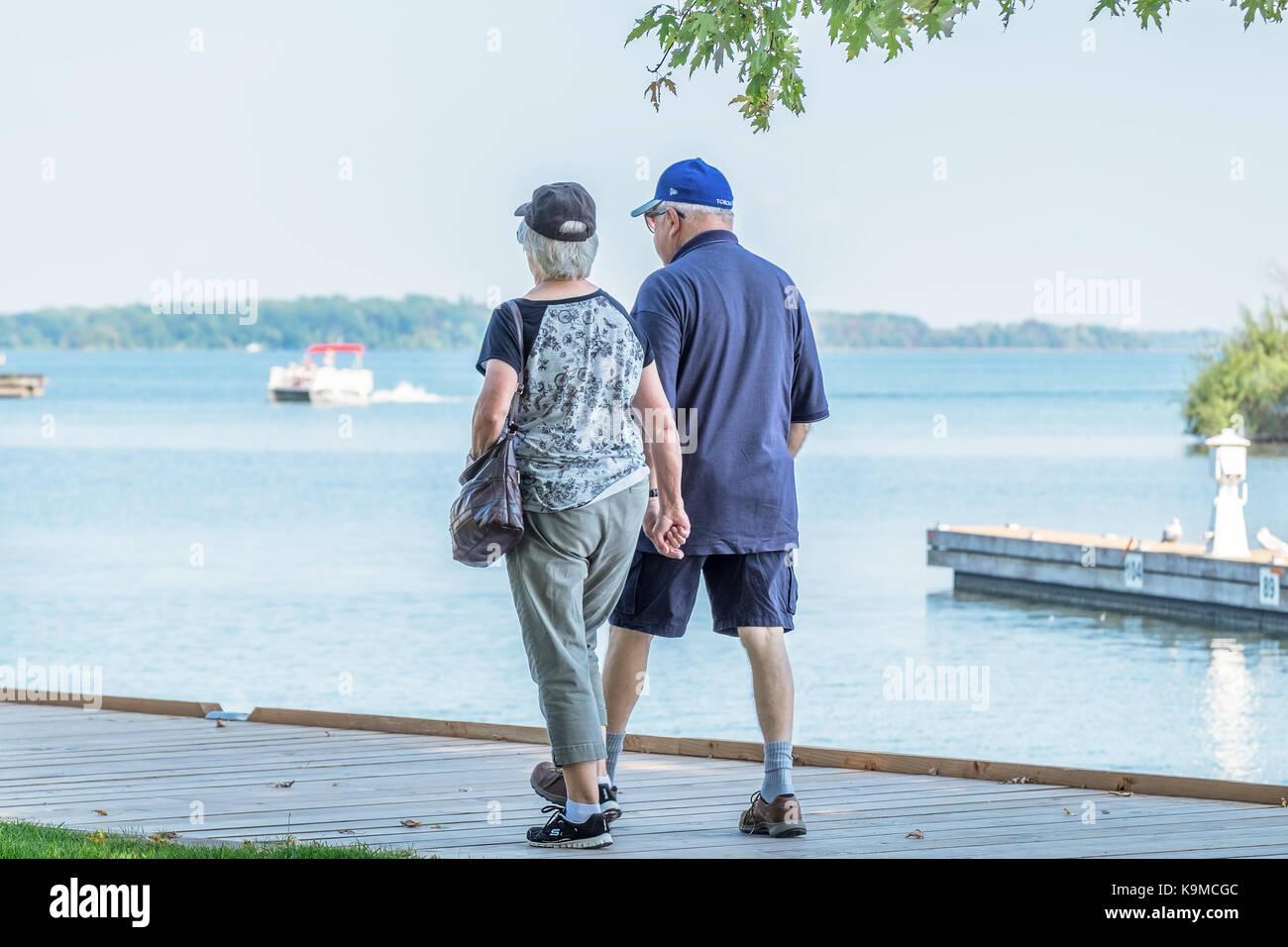 Senior couple marche main dans la main le long de la promenade au bord de l'eau à Orillia (Ontario) Canada. Photo Stock