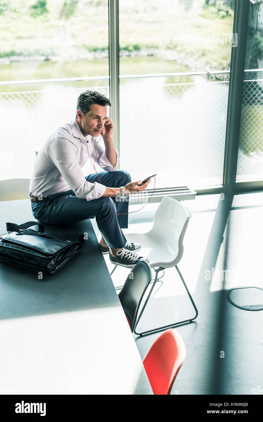 Businessman sitting on desk in office, using smartphone Photo Stock
