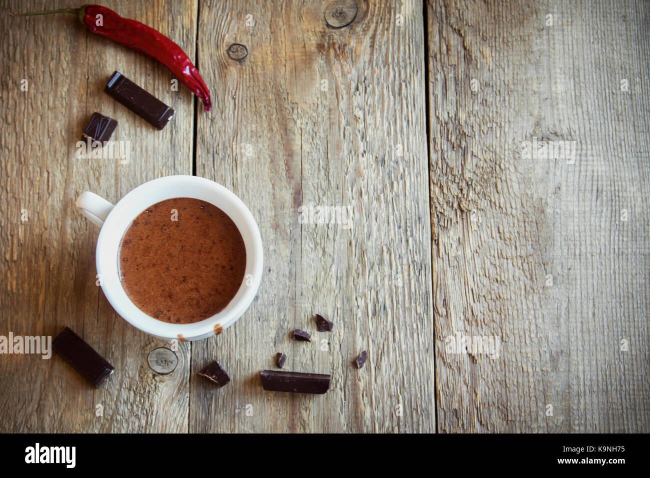 Chocolat chaud avec piment et pièces en chocolat sur fond de bois rustique. chocolat chaud maison verre pour Photo Stock