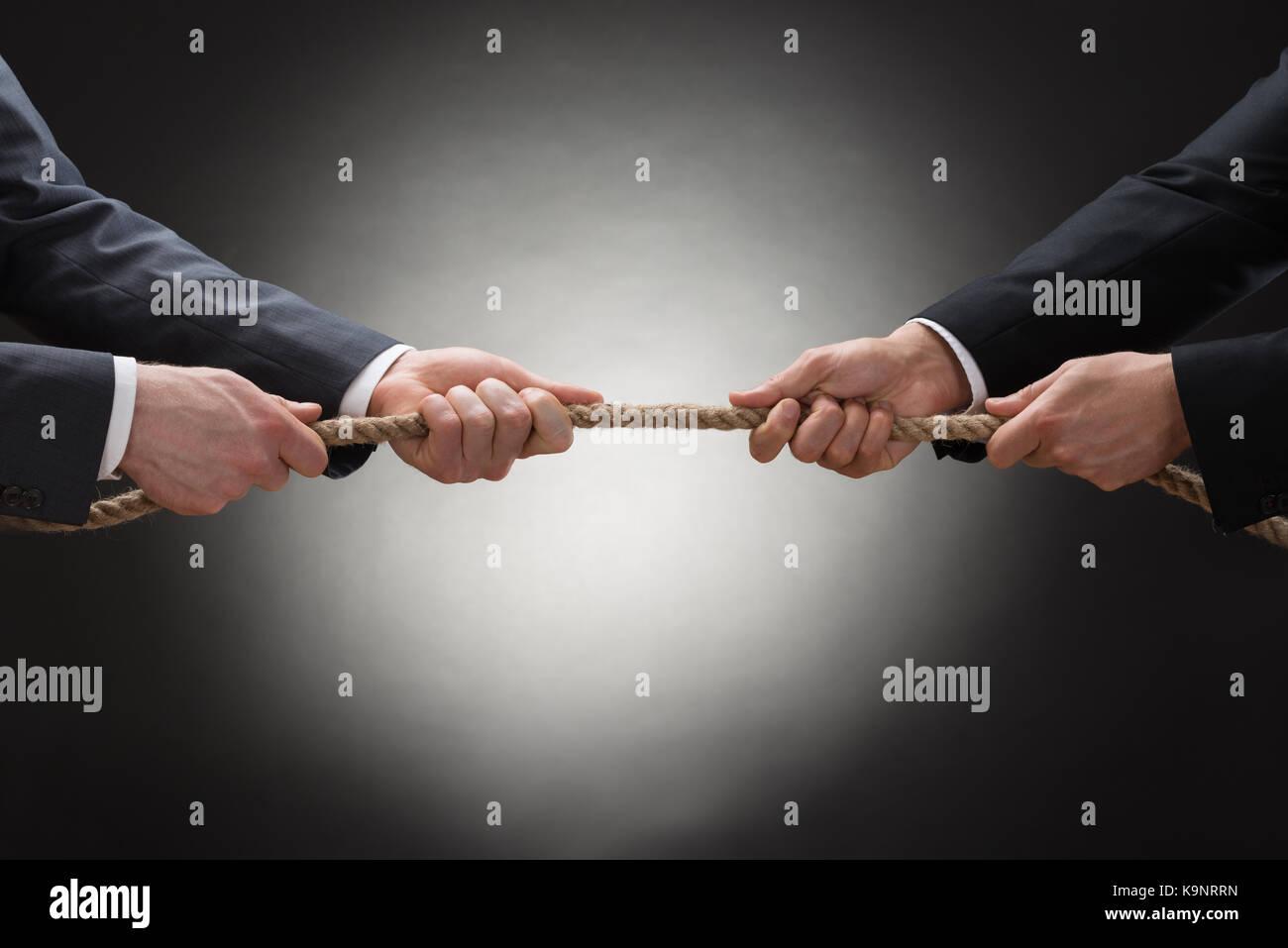 Close-up of a deux businessman pulling la corde dans l'autre sens Photo Stock