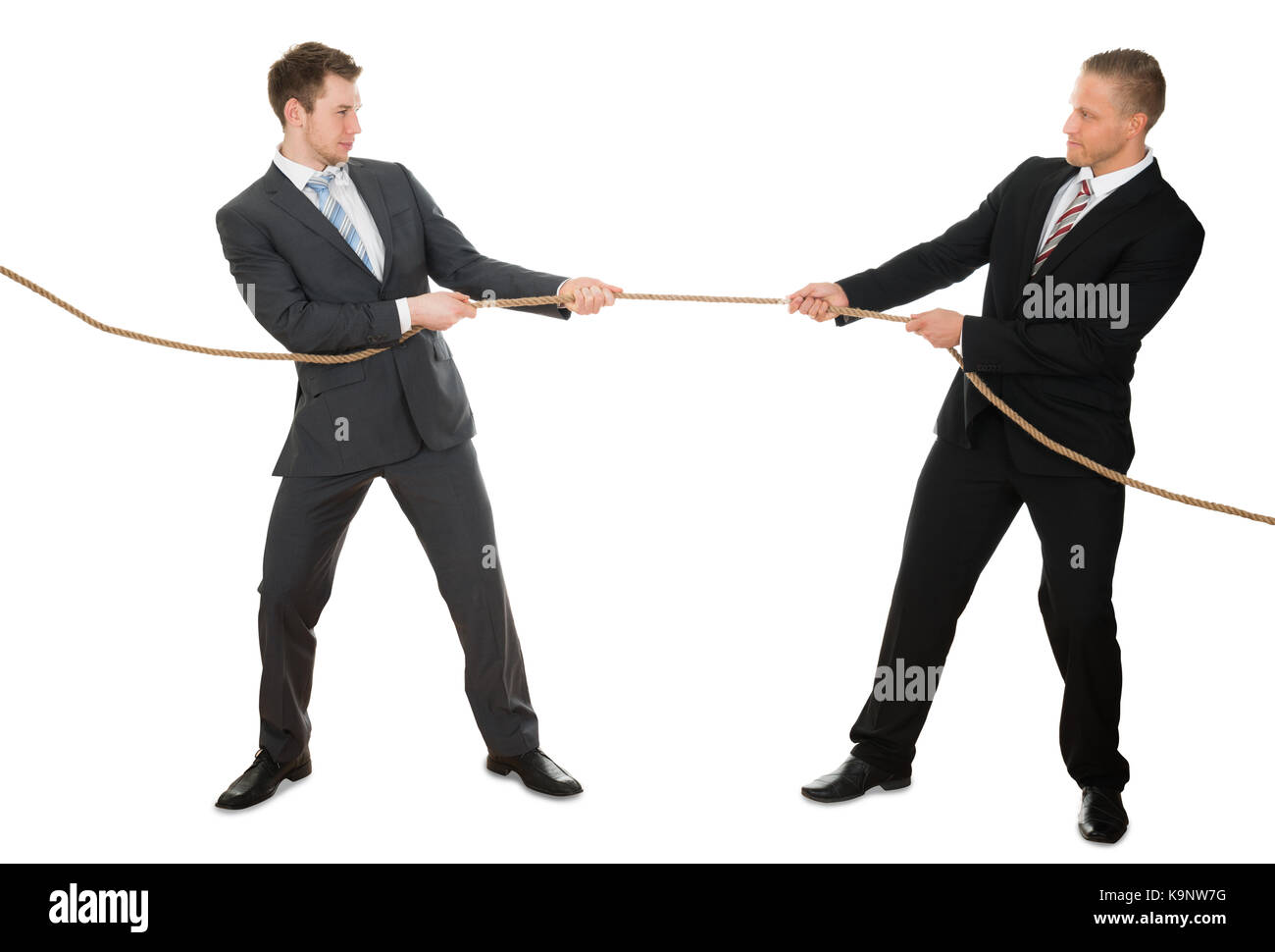 Portrait de deux businessman pulling corde sur fond blanc Photo Stock
