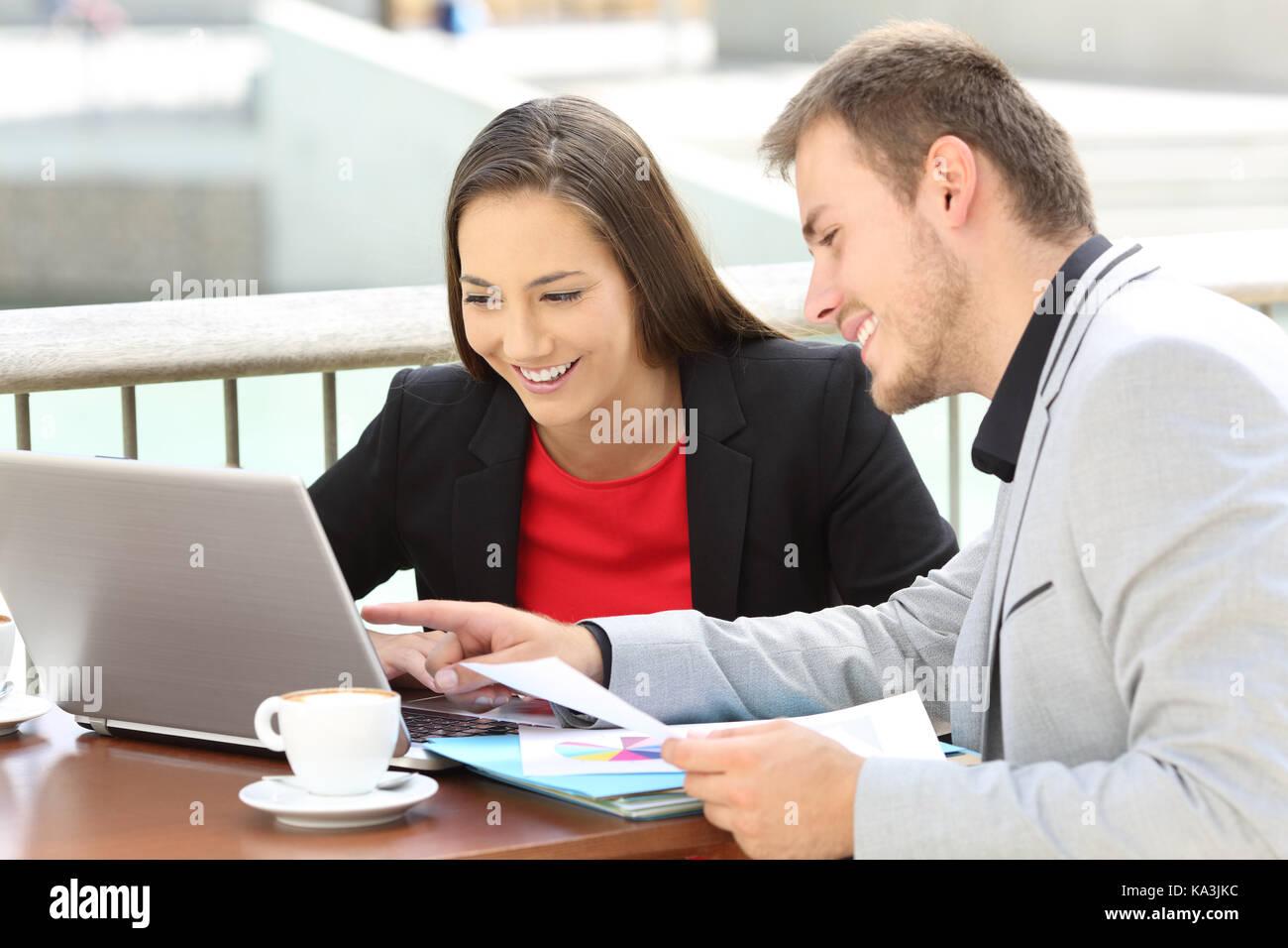 Deux cadres travaillant à la ligne avec un ordinateur portable assis dans un bar terrasse Photo Stock
