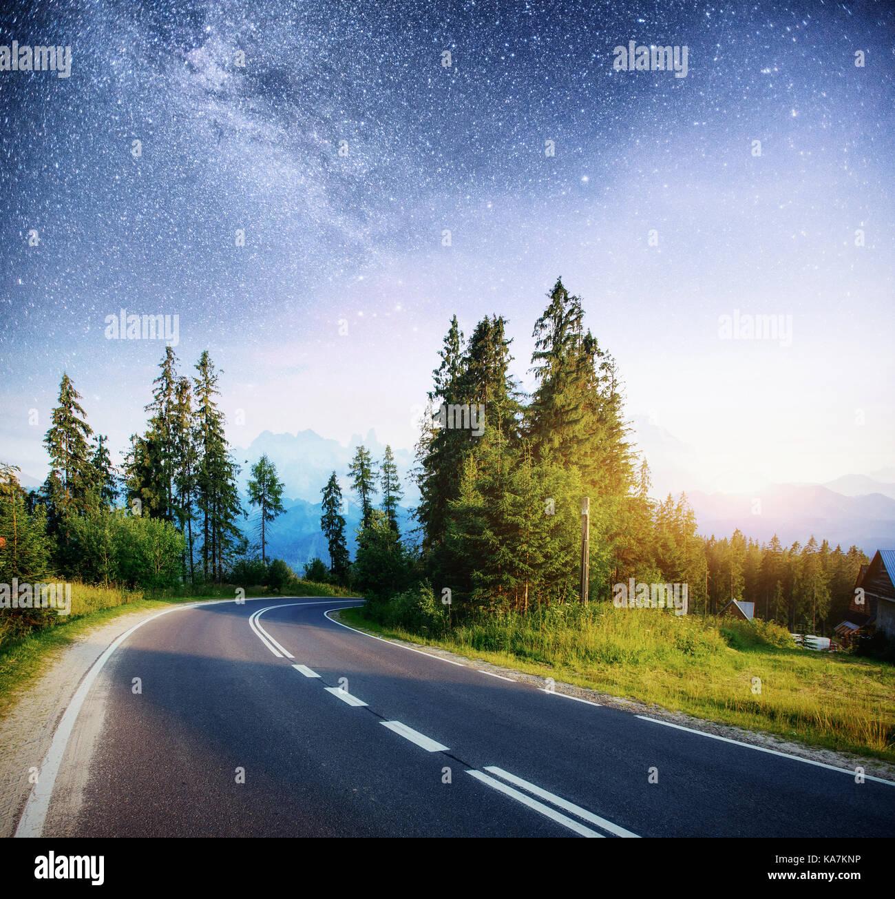 Route asphaltée sous un ciel étoilé et la voie lactée Photo Stock