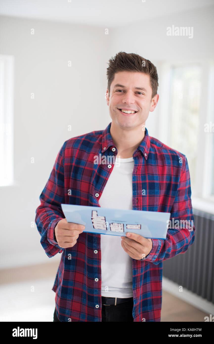 Man looking at brochure avec les détails pour nouvelle maison Photo Stock