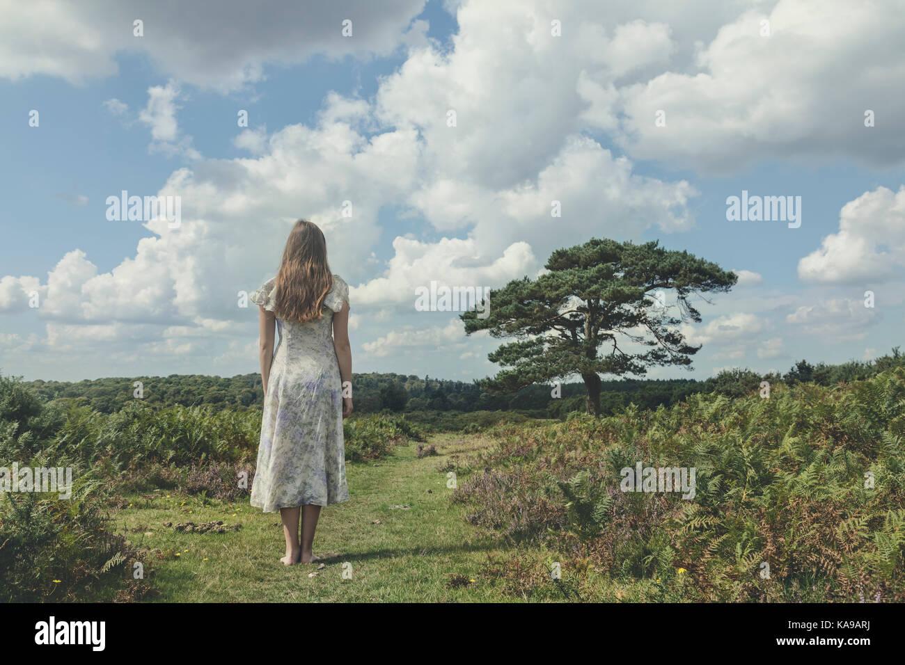 Une fille dans une robe florale est staning sur un champ à Bracken Banque D'Images