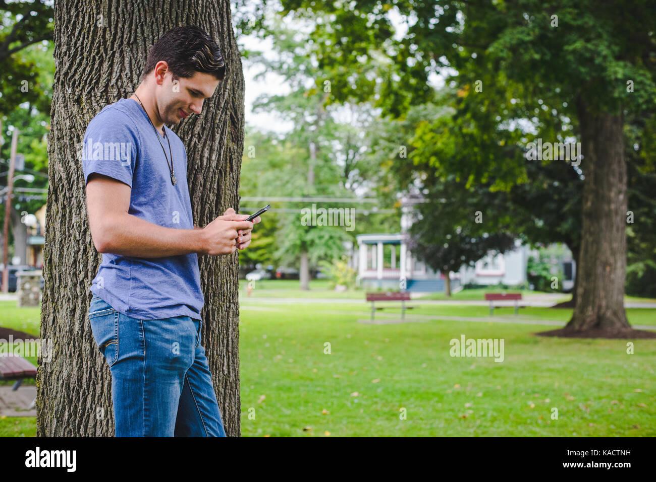 Un jeune homme regarde son téléphone cellulaire alors qu'appuyé contre un arbre dans un parc. Photo Stock