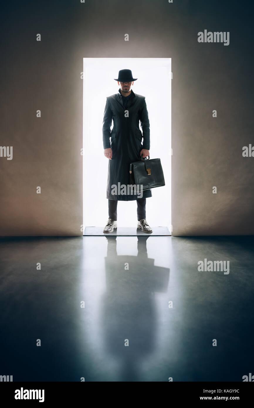 L'homme silhouette en imperméable et chapeau debout dans la lumière de l'ouverture de la porte Photo Stock