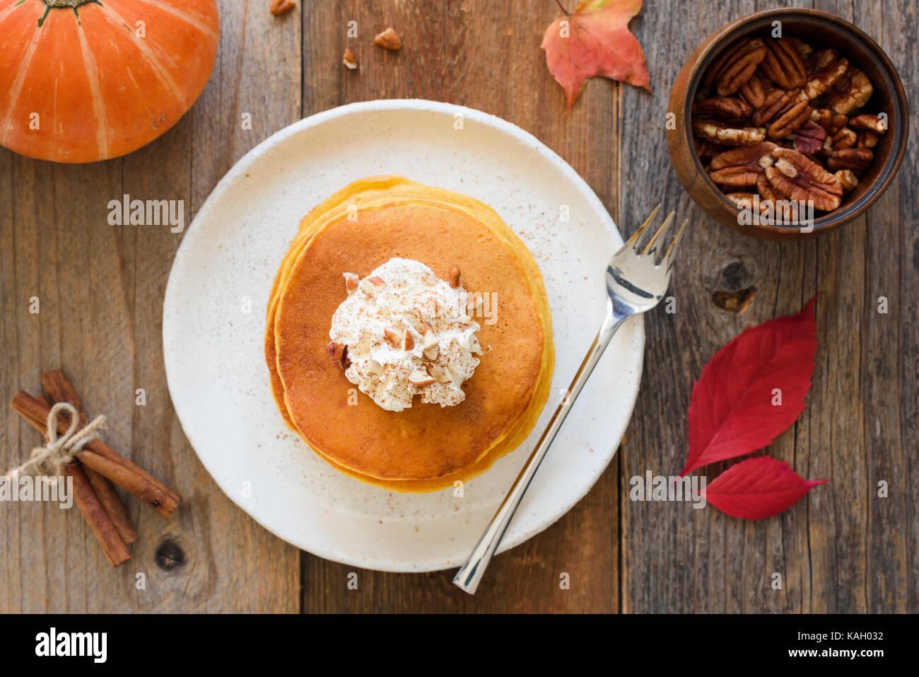 Crêpes à la citrouille avec crème fouettée et cannelle sur table en bois. vue d'en haut, Photo Stock