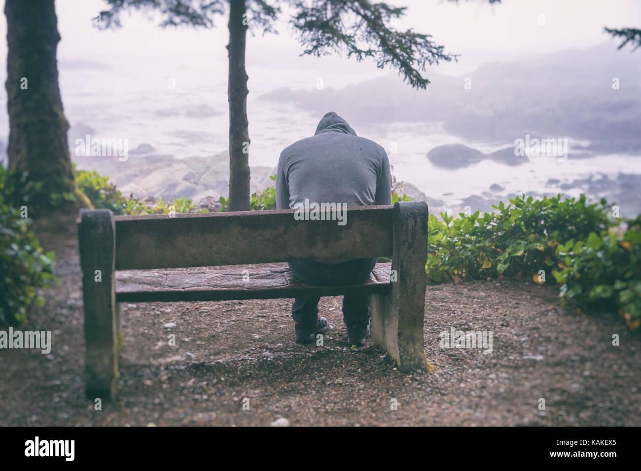 L'homme triste et solitaire assis sur un banc avec vue sur la mer sur l'île de Vancouver Photo Stock