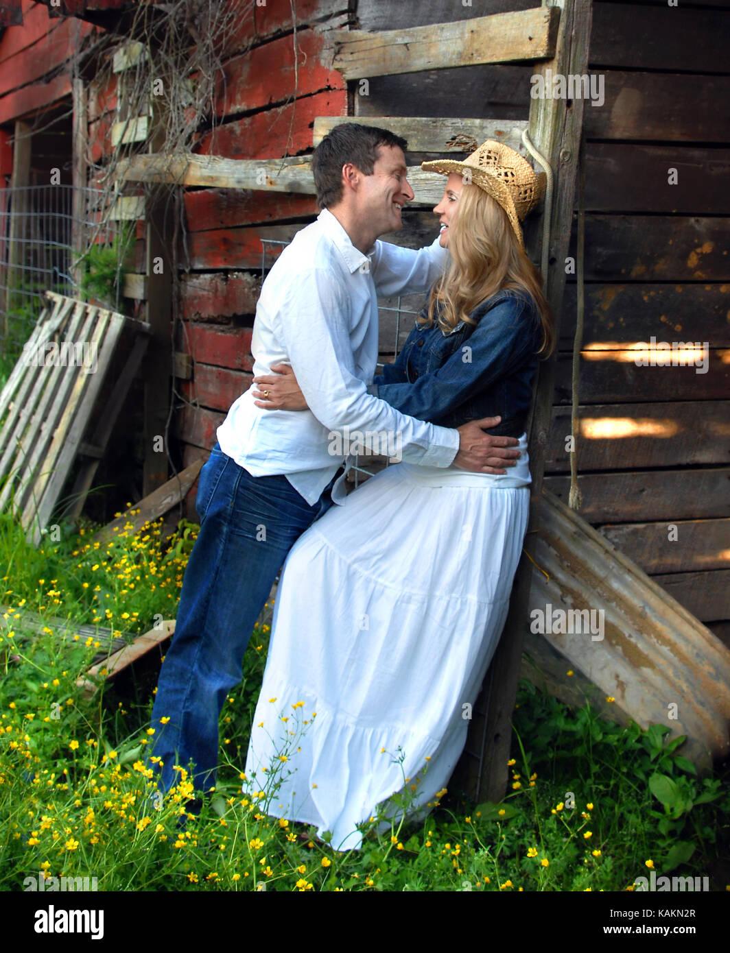 Jeune couple de discuter de leurs plans d'avenir qu'ils jouissent d'un moment romantique autour d'une grange rustique. Banque D'Images