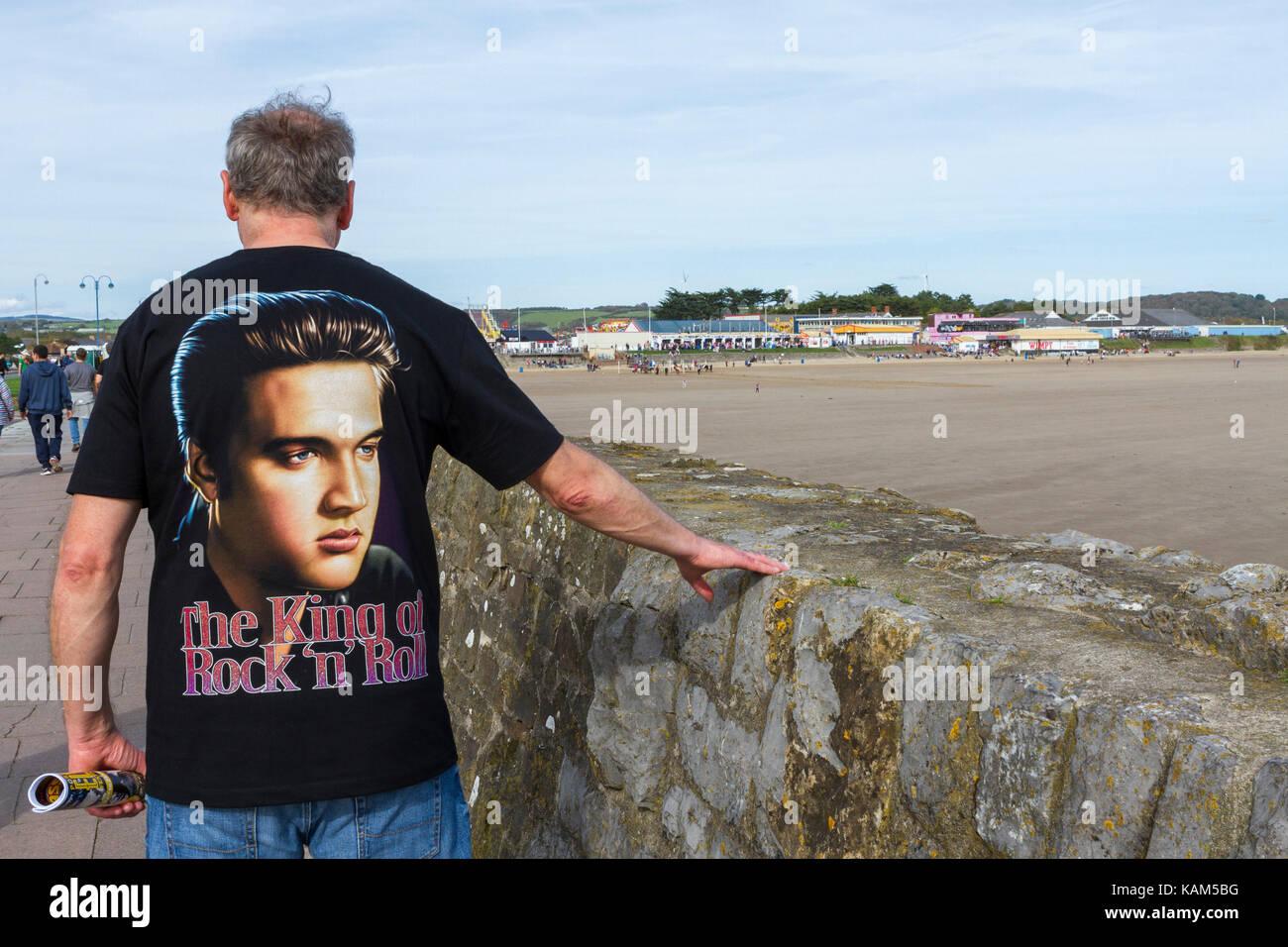 Homme portant un t-shirt Elvis Presley se dirige vers le Festival Elvis Porthcawl à Sandy Bay, Porthcawl, au Photo Stock