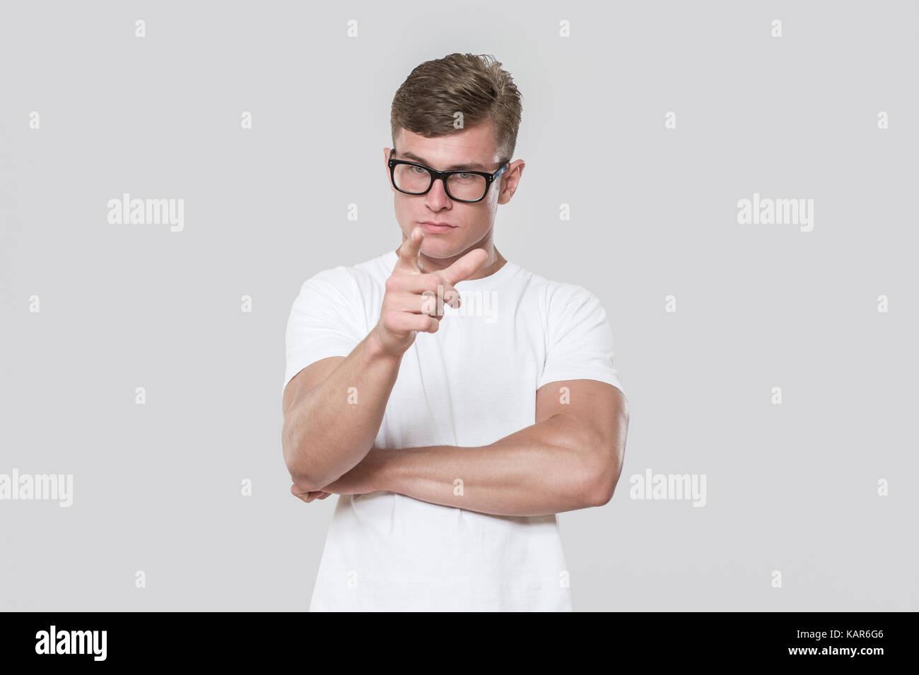 Beau jeune homme pointant à l'appareil photo. photo prise dans un studio avec fond gris. Le modèle Photo Stock