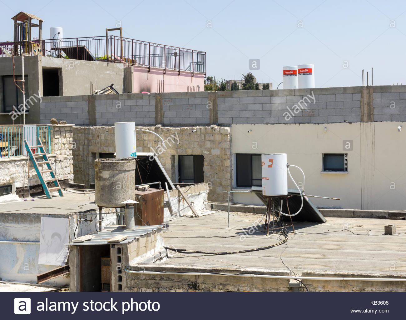 Passive-israélien standard chauffe-eau solaire, vu sur les toits de la ville de Safed, quartier Nord, Israël Photo Stock