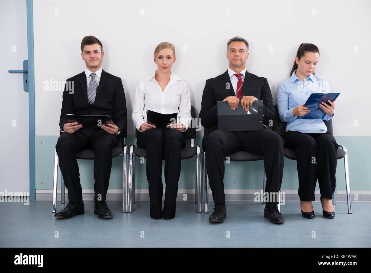 Groupe d'affaires avec des fichiers assis sur une chaise pour donner interview Photo Stock