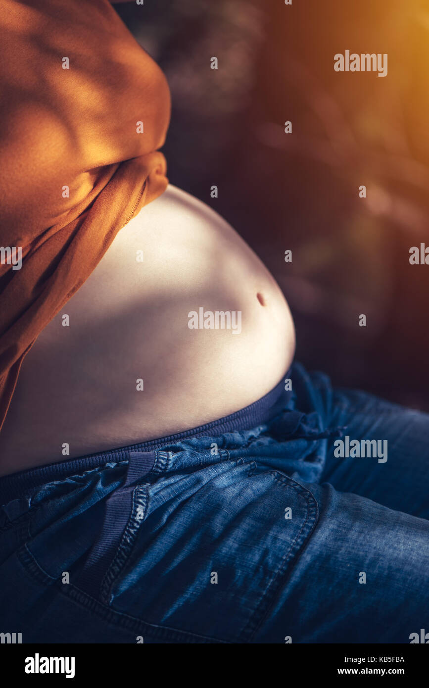 Femme enceinte se détendre et bronzer sur le ventre du soleil d'été chaude, selective focus Photo Stock