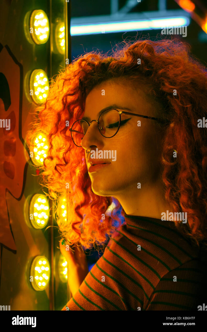 Portrait d'une jeune femme dans la nuit éclairé par des feux de couleur Photo Stock
