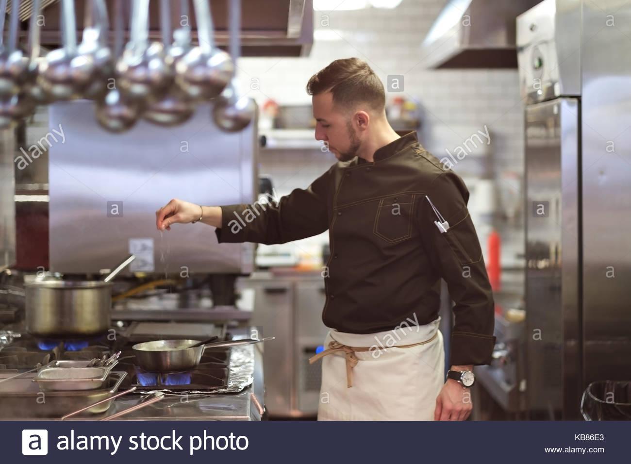 Concept alimentaire. Un jeune cuisinier se tient dans la cuisine et prépare un plat Photo Stock